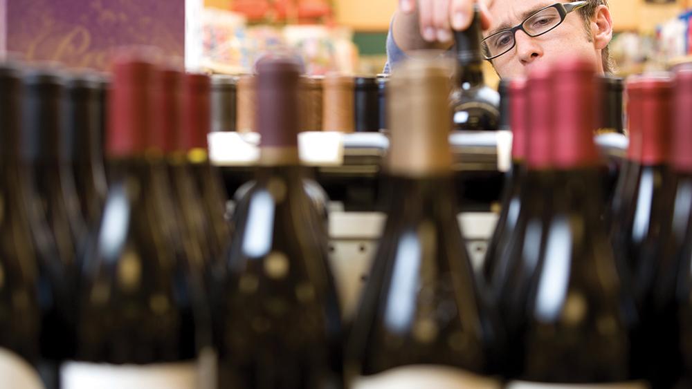 man examining bottles of wine on a shelf