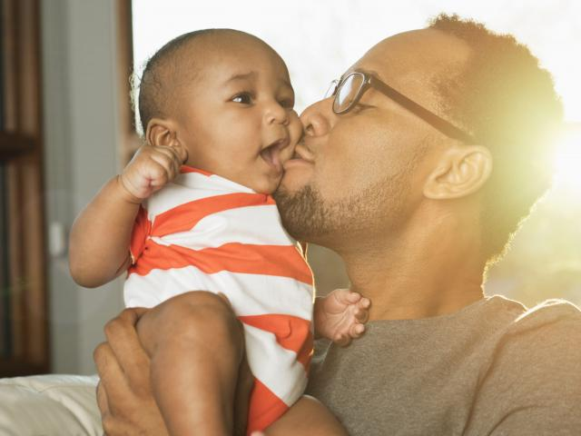 father kissing infant