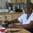 senior woman sitting at kitchen table in front of laptop