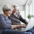happy senior couple on computer