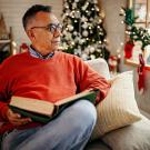 adult male senior reading book by Christmas tree